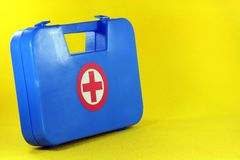 Blue first aid box. Helth and safe concepts first aid box in yellow background Royalty Free Stock Photos