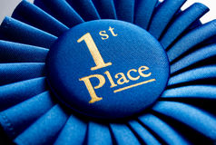 Blue first place winner rosette. Or badge from pleated ribbon with central text to be awarded to the winner of a competition on a graduated grey background with Royalty Free Stock Image