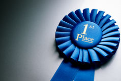 Blue first place winner rosette. Or badge from pleated ribbon with central text to be awarded to the winner of a competition on a graduated grey background with Royalty Free Stock Photos