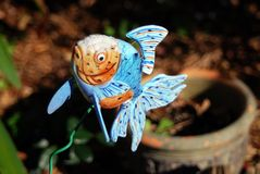Blue Fish. Blue and orange ceramic fish jumping out of a flower pot to get a breathe of fresh air...Gills not required.  This takes fly-fishing to a new extreme Royalty Free Stock Image