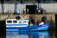 Blue Fishing boat alongside the wharf. stock photo