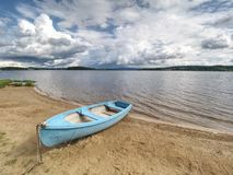 Free Blue Fishing Boat Anchored On Beach Sand Of Lake. Smooth Level Royalty Free Stock Images - 155035179