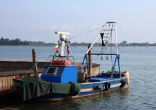 blue fishing boat moored at the port of the island of Burano stock photos