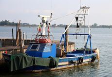 blue fishing boat moored in the port of an island near Venice royalty free stock images