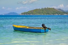 Blue fishing boat with outboard motor on turquoise ocean royalty free stock images
