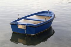 Blue fishing boat stands on a quiet lake.  stock photos