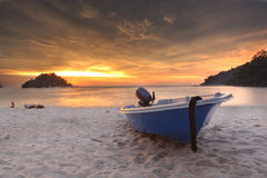 Blue fishing boat at sunset on the beach Royalty Free Stock Photo