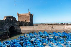 Blue Fishing boats and defensive tower in Essaouira - Morocco stock photo
