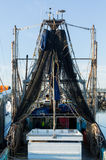 Blue fishing nets or trawl hanging from ship Stock Image