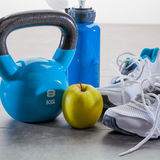Blue fitness accessories with still-life of sneakers and kettle bell Royalty Free Stock Image