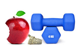 Blue fitness dumbbells with bitten red apple Royalty Free Stock Images