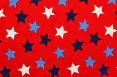 Blue five-pointed stars on red fabric. Stock Photography