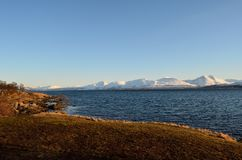 Blue fjord and snowy mountain range Stock Image