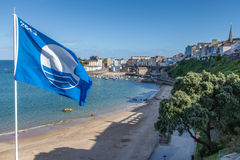 Blue Flag Beach at Tenby, Pembrokeshire. Showing the clue flag waving in the wind and the town behind Stock Photo
