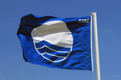 Blue flag is flying on the beach... White flag means, that is accessible and beach for everyone. The Blue Flag is a certification for a beach meets the Stock Images