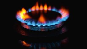 Blue flame of gas stove on black background. Kitchen burner turning on. Natural gas inflammation. chemical reaction. Staining the