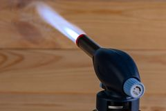 Blue flame with a manual gas burner on the wooden background. Close-up royalty free stock photos
