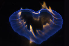 Blue flame in the shape of heart burning on shiny surface Royalty Free Stock Images
