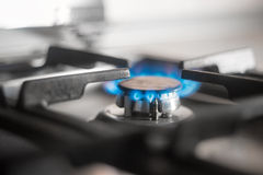 Blue flames of gas burning from a kitchen gas stove. Selective focus. Royalty Free Stock Photography