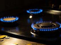 Blue flames on gas stove burner. Natural gas burning blue flames on black background stock image