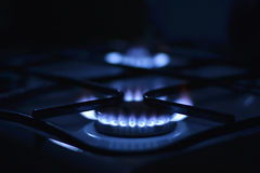 Blue flames of gas. Stove in the dark. Shallow depth of field Stock Image