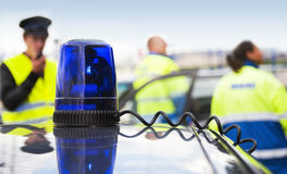 Blue flashing light. On an unmarked police car, with three people from Emergency Medical Services in the background Stock Image