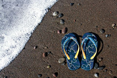 Blue flip-flop sandals on the beach Stock Image