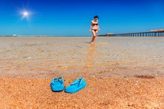 Blue flip flop, sea. Blue flip flop sandals in the sand on the sea beach. Young girl in the water royalty free stock image
