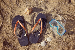 Blue flip flop and the snorkel mask. Blue flip flop and the snorkel diving mask on the sand, flat lay view. Summer entertainment concept Royalty Free Stock Image