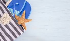 Blue flip flops in beach bag and starfish on light blue background with copy space. Top view royalty free stock photos