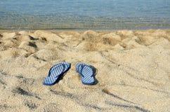 Blue flip flops on a beach Stock Image