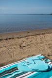 Blue Flip Flops on Beach Towel Lake Michigan. Blue flip flops on a beach towel in the sand on the shore of Lake Michigan vertical Royalty Free Stock Image