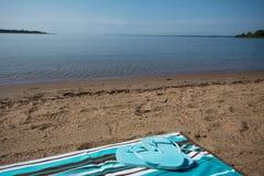 Blue Flip Flops on Beach Towel Lake Michigan Shore. Blue flip flops on a beach towel in the sand on the shore of Lake Michigan horizontal Stock Photo
