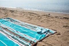 Blue Flip Flops on Beach Towel Lake Michigan Shoreline. Blue flip flops on a beach towel in the sand on the shore of Lake Michigan with wave in background Stock Photos