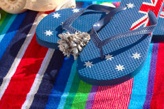 Blue flip flops on beach towel Stock Photos
