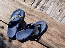 Blue flip flops on the brown wooden floor with natural day light Royalty Free Stock Photo