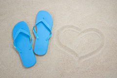 Blue flip flops and heart on sandy beach Royalty Free Stock Images