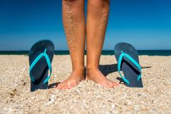 Blue flip-flops and human legs on the sand - a concept for summer vacation, travel and leisure Royalty Free Stock Photos