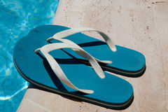 Blue flip-flops near the pool Stock Image