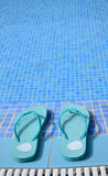 Blue flip flops near pool Royalty Free Stock Photography