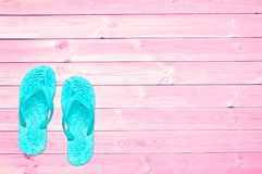 Blue flip flops on pink planks, summer concept background. With copy space Royalty Free Stock Image