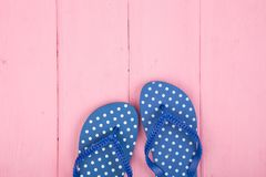 Flip flops in polka dots on pink wooden background. Blue flip flops in polka dots on pink wooden background royalty free stock images