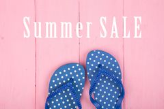 Blue flip flops in polka dots and text Summer sale on pink. Wooden background, sea, beach, desk, fashion, holiday, leisure, pair, sandals, travel, tropical stock photos