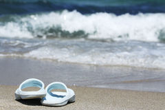 Blue flip flops on sand beach in front of sea wave Stock Images