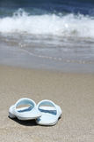 Blue flip flops on sand beach in front of sea wave Royalty Free Stock Images