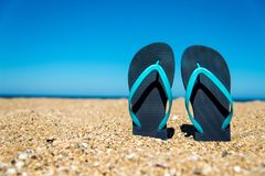 Blue flip-flops on the sand - a concept for summer vacation, travel and leisure Royalty Free Stock Photos