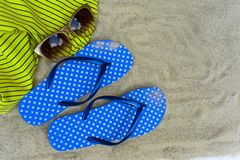 Blue  flip flops,  on sandy beach with seashells stock photo