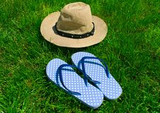 Blue flip flops and summer hat on green grass. stock photography