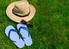 Blue flip flops and summer hat on green grass. stock image