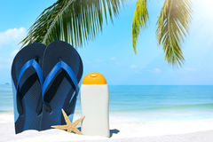 Blue Flip Flops and suntan lotion. Blue flip flops, suntan lotion and sea star under palm frond on the beach stock photos